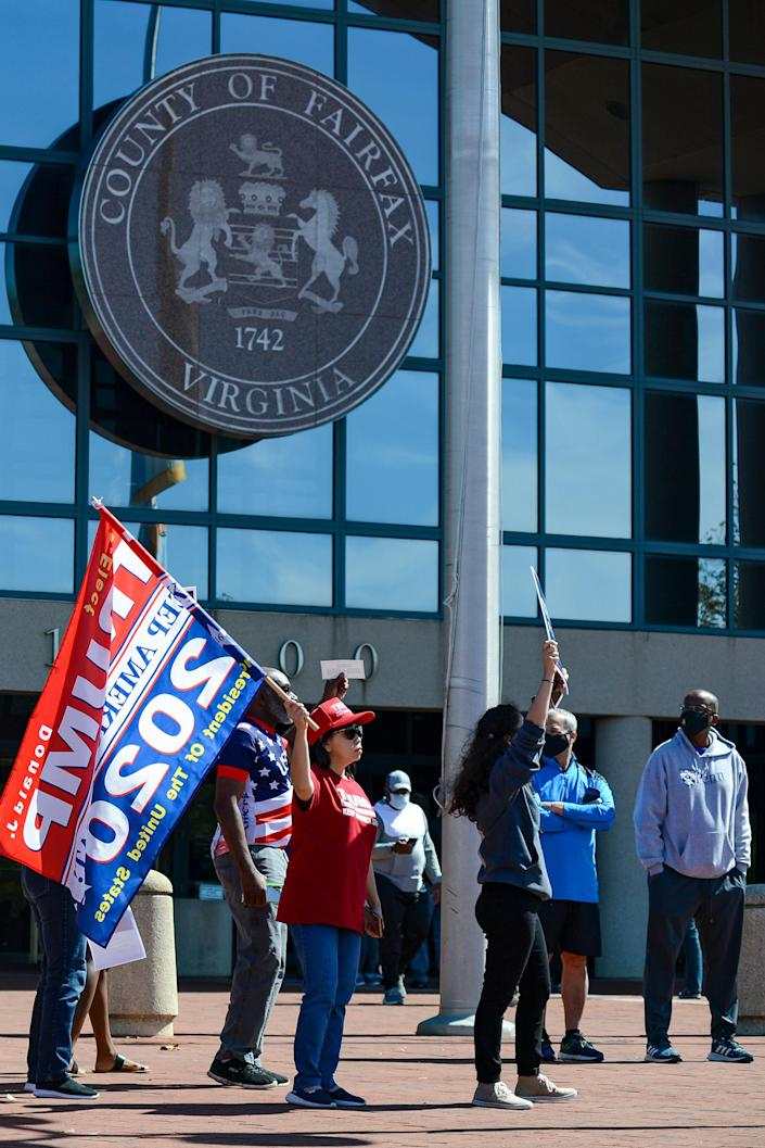 """Trump supporters chant, """"Four more years,"""" on Sept.19 outside the Fairfax County Government Center in Fairfax, Va., disrupting early voting"""