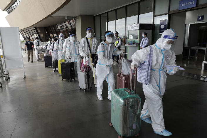 Foreign passengers wearing protective suits walk for their flight to China at Manila's International Airport, Philippines, Monday, Jan. 18, 2021. Coronavirus infections in the Philippines have surged past 500,000 in a new bleak milestone with the government facing criticisms for failing to immediately launch a vaccination program amid a global scramble for COVID-19 vaccines. (AP Photo/Aaron Favila)