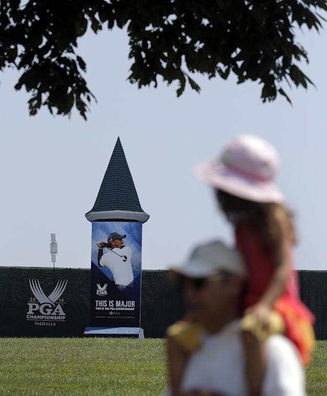 Golf fan Nevin Baker carries his daughter, Sophia, 4, on his shoulders as they walk past a photo of Tiger Woods at the PGA Championship golf tournament at Valhalla Golf Club Monday, Aug. 4, 2014, in Louisville, Ky. The tournament is set to begin on Thursday. (AP Photo/Jeff Roberson)