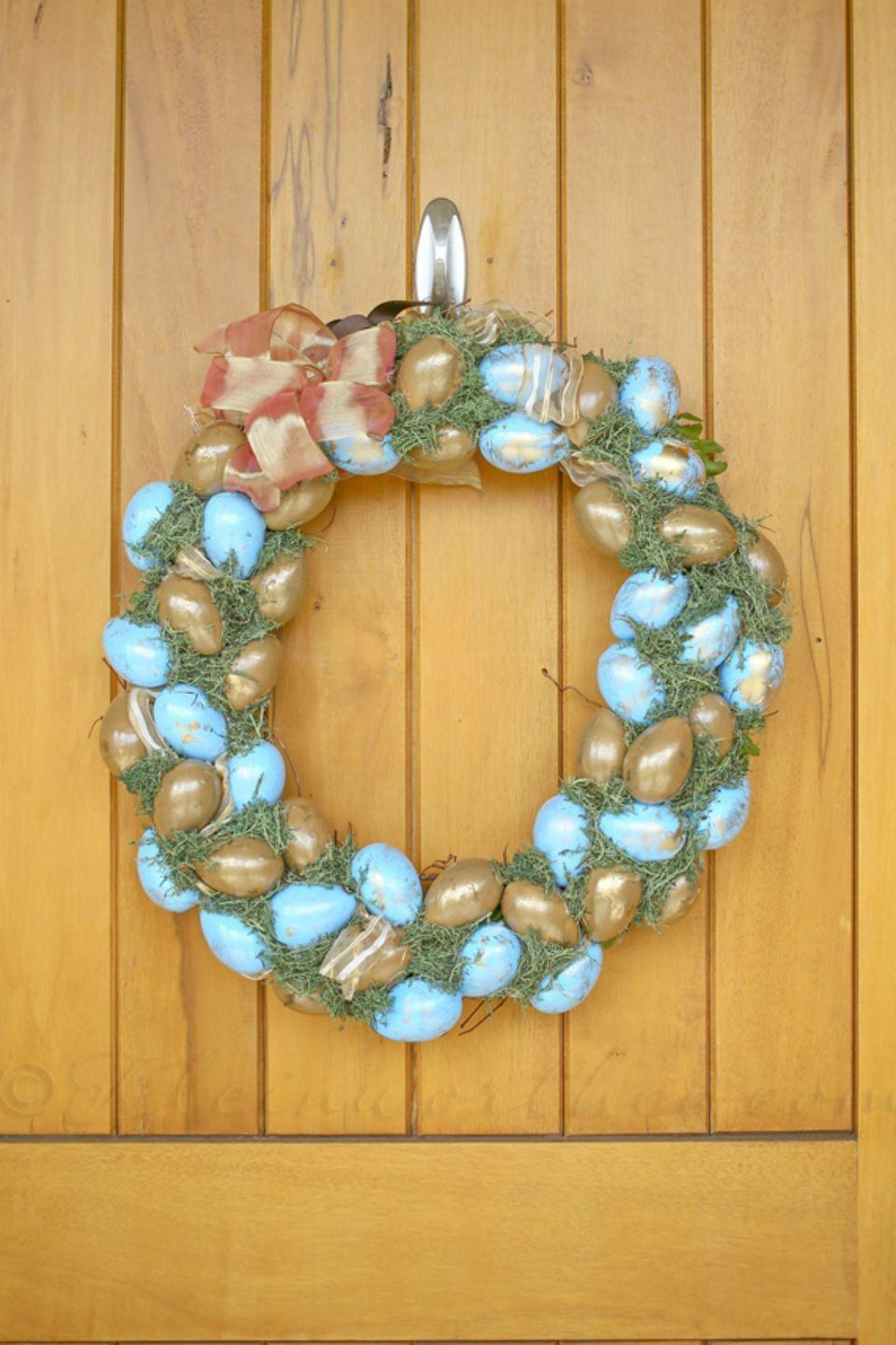 """<p>Spray paint half of your eggs blue and half of them gold, filling the gaps with reindeer moss.</p><p><strong>Get the tutorial at <a href=""""http://www.kleinworthco.com/2014/04/blue-gold-easter-wreath.html"""" rel=""""nofollow noopener"""" target=""""_blank"""" data-ylk=""""slk:Kleinworth & Co"""" class=""""link rapid-noclick-resp"""">Kleinworth & Co</a>. </strong><br></p><p><strong><a class=""""link rapid-noclick-resp"""" href=""""https://www.amazon.com/Gigules-Imitation-Painting-Crafting-Decoration/dp/B07CQD174T?tag=syn-yahoo-20&ascsubtag=%5Bartid%7C10050.g.4088%5Bsrc%7Cyahoo-us"""" rel=""""nofollow noopener"""" target=""""_blank"""" data-ylk=""""slk:SHOP GOLD LEAF"""">SHOP GOLD LEAF </a><br></strong></p>"""