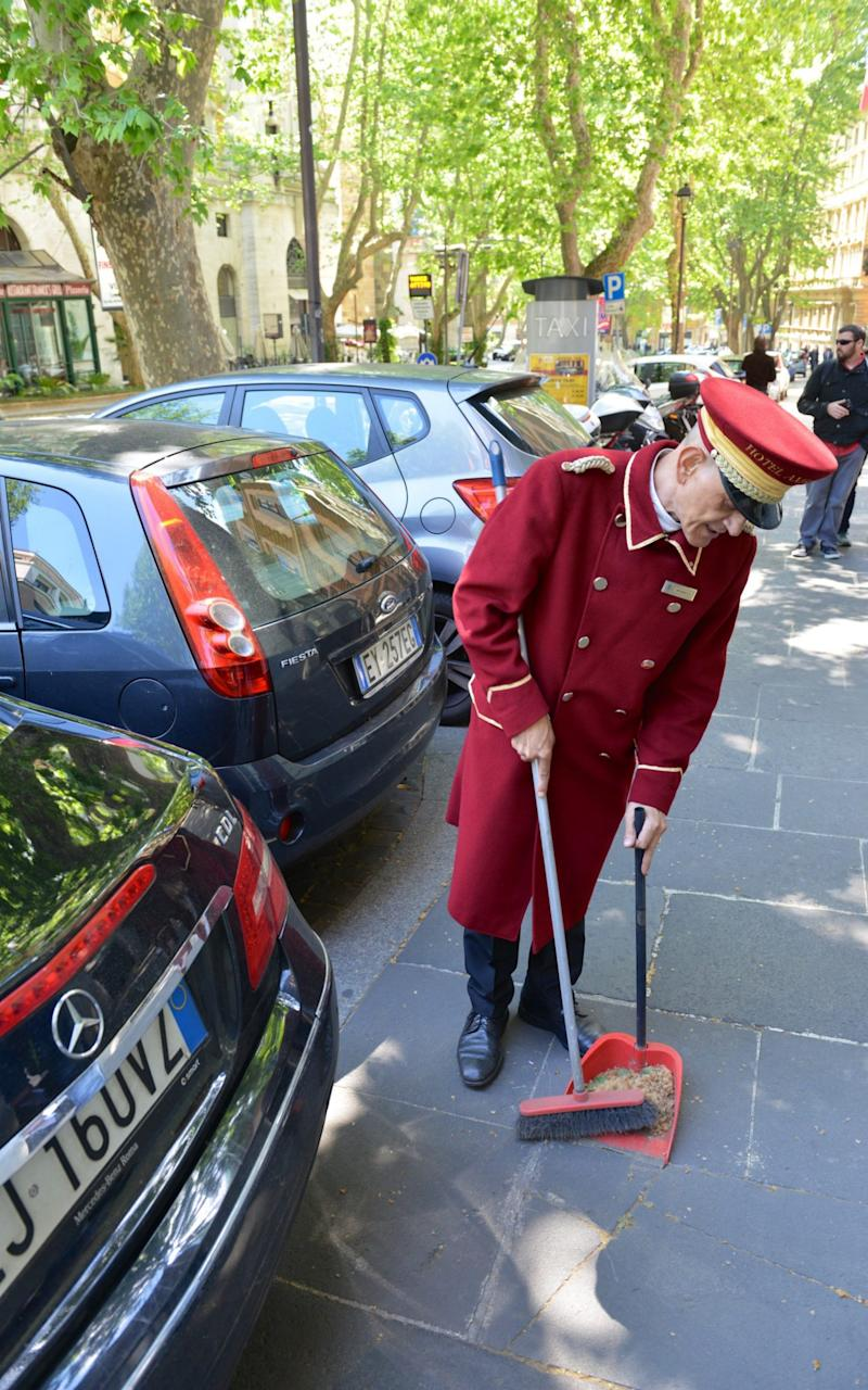 A hotel doorman sweeps a pavement blocked by illegally parked cars on Via Veneto, once the symbol of the Dolce Vita in post-war Italy. - Credit: Chris Warde-Jones