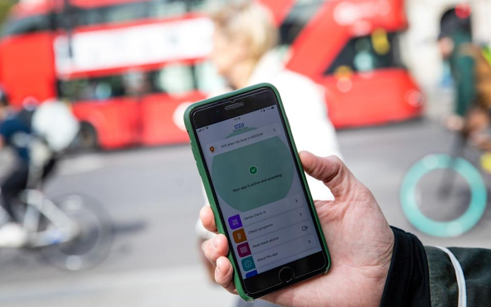 A smartphone displays a screen from the newly released 'NHS COVID-19' contract tracing app in view of traffic in this arranged photograph in London, U.K. - Simon Dawson/Bloomberg