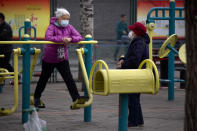 A woman wearing a face mask to protect against the coronavirus uses an exercise machine at a public park in Beijing, Thursday, March 18, 2021. China has been regularly reporting no locally transmitted cases of COVID-19 as it works to maintain control of the pandemic within its borders. (AP Photo/Mark Schiefelbein)
