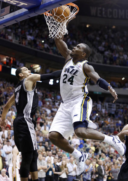 Utah Jazz forward Paul Millsap (24) dunks in front of San Antonio Spurs guard Daniel Green (4) during the second half of an NBA basketball game Monday, April 9, 2012, in Salt Lake City. The Jazz won 91-84. (AP Photo/Jim Urquhart)