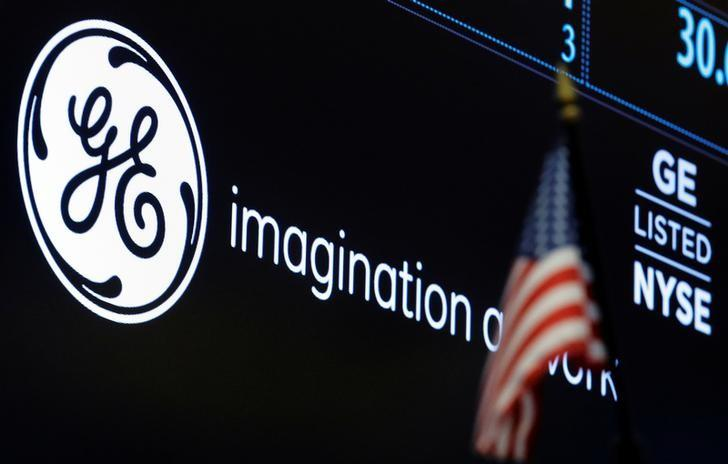 FILE PHOTO - The ticker and logo for General Electric Co. is displayed on a screen at the post where it's traded on the floor of the NYSE