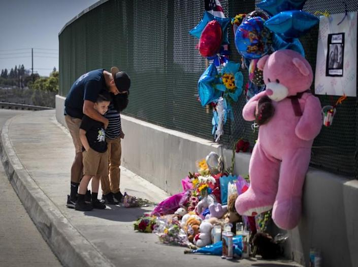 """Orange, CA - May 22: George Aguilar prays with his sons, Jackson, 7, and Jacob, 11, of Anaheim, as they place flowers on a growing memorial on the Walnut Ave. overpass of the 55 Freeway, where 6-year-old boy died after being shot in an apparent road-rage incident Friday morning on the northbound 55 Freeway near the Chapman Ave. exit in 55 Freeway on Saturday, May 22, 2021 in Orange, CA. """"I wanted to pay my respects and bring flowers, said Aguilar. """"That could have been one of my kids."""" The gunman and accomplice remain at large. Officials are searching for a newer white sedan, possibly a """"Volkswagen wagon sedan,"""" that fled north on the 55 Freeway, (Allen J. Schaben / Los Angeles Times)"""