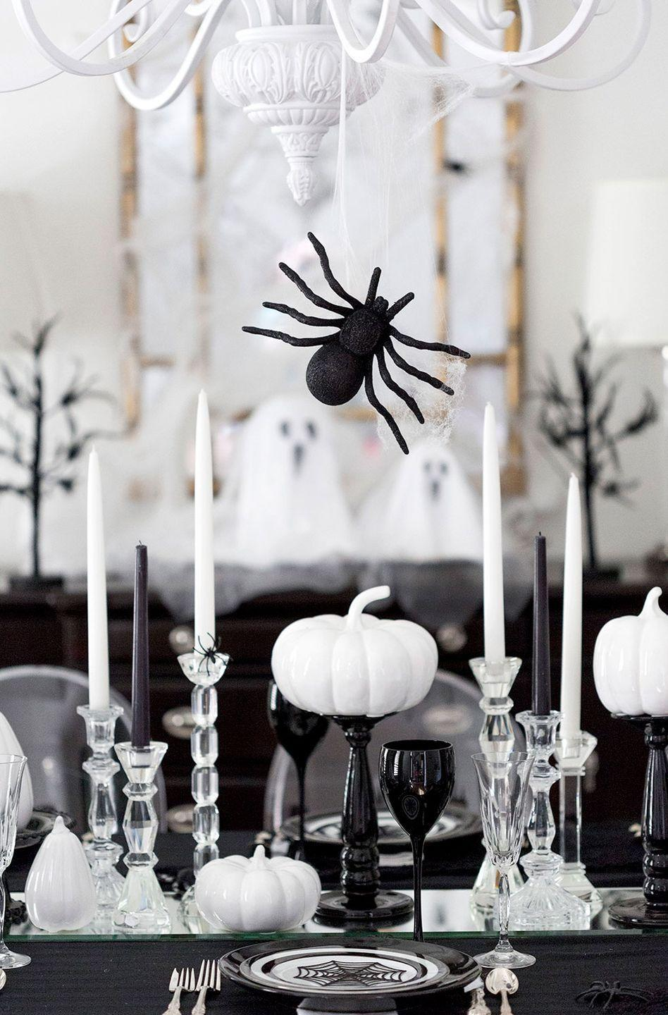 """<p>Black-and-white dinnerware, pumpkins, and candles create an elevated, but still spirited, display. </p><p><strong>Get the tutorial at <a href=""""https://pizzazzerie.com/featured/host-a-spooktacular-halloween-dinner-party/"""" rel=""""nofollow noopener"""" target=""""_blank"""" data-ylk=""""slk:Pizzazzerie"""" class=""""link rapid-noclick-resp"""">Pizzazzerie</a>.</strong></p><p><a class=""""link rapid-noclick-resp"""" href=""""https://www.amazon.com/Factory-Direct-Craft-Artificial-Thanksgiving/dp/B01KGCGQA4/?tag=syn-yahoo-20&ascsubtag=%5Bartid%7C10050.g.3739%5Bsrc%7Cyahoo-us"""" rel=""""nofollow noopener"""" target=""""_blank"""" data-ylk=""""slk:SHOP FAUX WHITE PUMPKINS"""">SHOP FAUX WHITE PUMPKINS</a> </p>"""