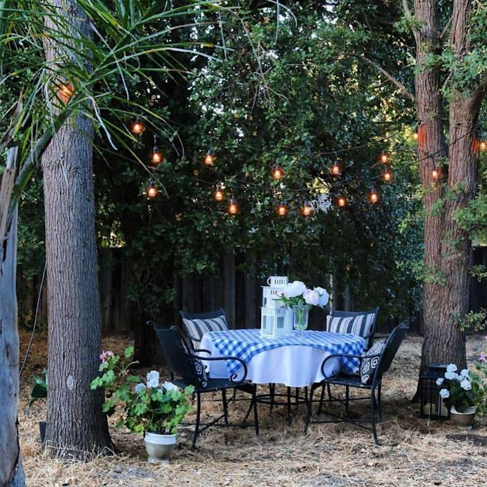 """<p>If you're working with a wooded backyard, make use of nature and string lights from the branches. Place a table and chairs underneath for the perfect summertime dinner party setup.</p><p><strong>See more at <a href=""""https://www.instagram.com/p/B0mkHxgAKxT/?igshid=1f89v5fb2zp7j"""" rel=""""nofollow noopener"""" target=""""_blank"""" data-ylk=""""slk:jodie.thedesigntwins"""" class=""""link rapid-noclick-resp"""">jodie.thedesigntwins</a>.</strong></p><p><a class=""""link rapid-noclick-resp"""" href=""""https://www.amazon.com/Outdoor-Commercial-Waterproof-Dimmable-Backyard/dp/B07HSYVD1M/?tag=syn-yahoo-20&ascsubtag=%5Bartid%7C10050.g.31137877%5Bsrc%7Cyahoo-us"""" rel=""""nofollow noopener"""" target=""""_blank"""" data-ylk=""""slk:SHOP STRING LIGHTS"""">SHOP STRING LIGHTS</a></p>"""