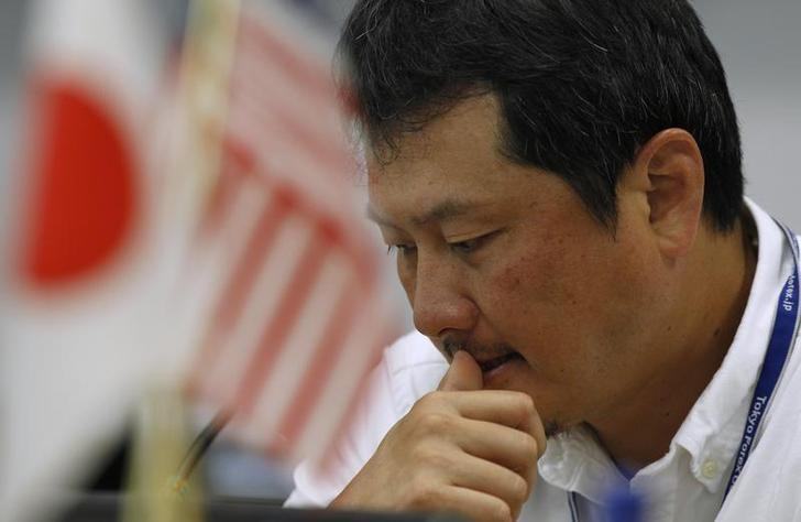 A foreign exchange broker rests his thumb on his lips as he is pictured near Japanese and American flags at a trading room in Tokyo October 26, 2011. REUTERS/Yuriko Nakao/Files