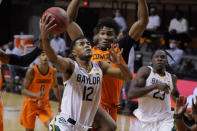 Baylor guard Jared Butler (12) goes to the basket in front of Oklahoma State forward Matthew-Alexander Moncrieffe, rear, in the first half of an NCAA college basketball game Saturday, Jan. 23, 2021, in Stillwater, Okla. (AP Photo/Sue Ogrocki)