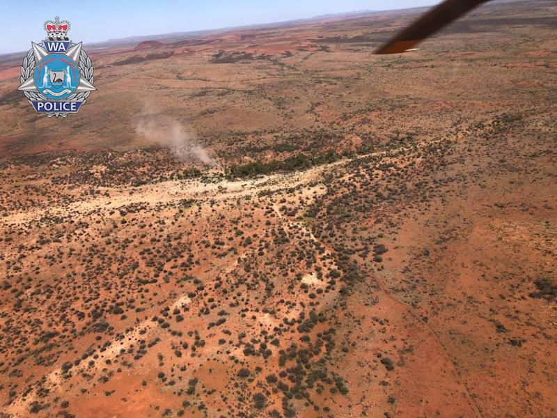 An aerial view of the WA man's makeshift campsite with smoke billowing into the air.