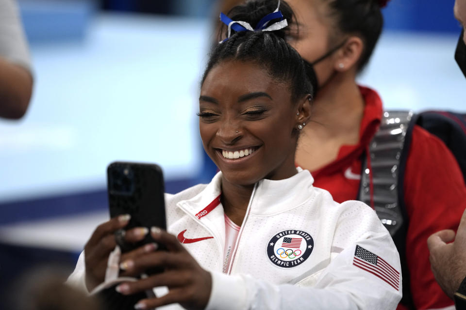 Simone Biles, of the United States, talks on the phone after participating on the balance beam during the artistic gymnastics women's apparatus final at the 2020 Summer Olympics, Tuesday, Aug. 3, 2021, in Tokyo, Japan. (AP Photo/Ashley Landis)