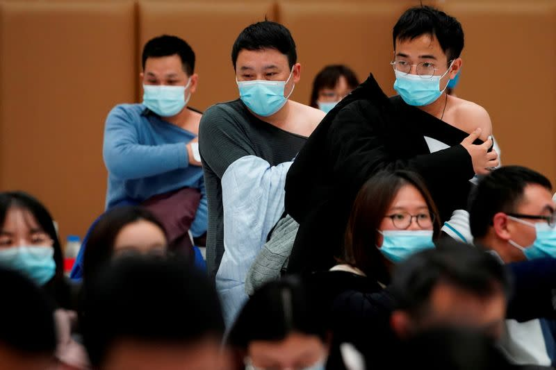 FILE PHOTO: People stand at a vaccination site after receiving a dose of a coronavirus disease (COVID-19) vaccine, in Shanghai