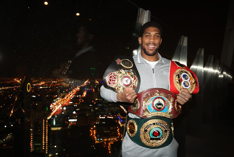 Anthony Joshua poses for photographers with his WBA, IBF, WBO and IBO championship belts on the viewing gallery of the Al Faisaliah Centre in Riyadh, Saudi Arabia. (Photo by Nick Potts/PA Images via Getty Images)