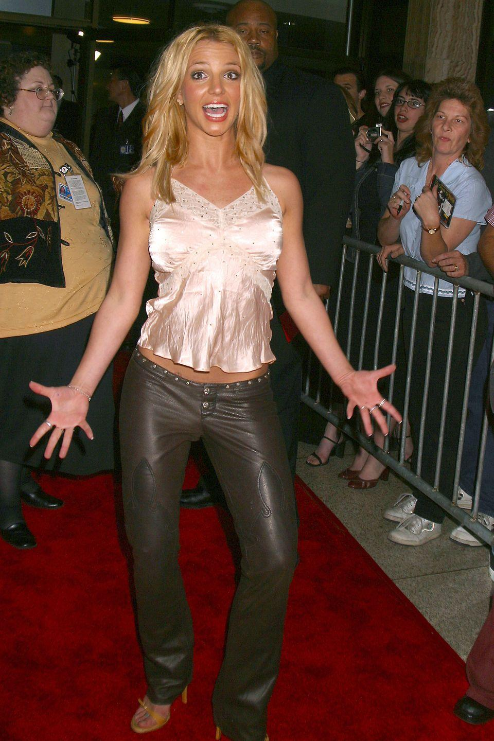 <p>Here, Brit wears low-rise leather pants, a lacy camisole, and strappy sandals to a red-carpet event.</p>