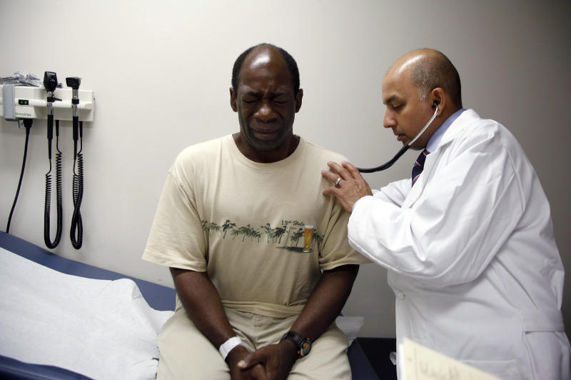 Ernest Sass, 52, (L) winces as he is attended to by Girish Bobby Kapur, M.D. (R) in a room used to see patients who don't require treatment for trauma inside the emergency room at Ben Taub General Hospital in Houston, Texas July 27, 2009. Houston, the fourth-largest American city, is a case study in the extremes of the U.S. healthcare system. It boasts the immense medical center that offers top-notch care at its 13 hospitals, but also has a higher ratio of uninsured patients than any major U.S. city: about 30 percent. To match feature USA-HEALTHCARE/TEXAS REUTERS/Jessica Rinaldi (UNITED STATES SOCIETY HEALTH POLITICS)