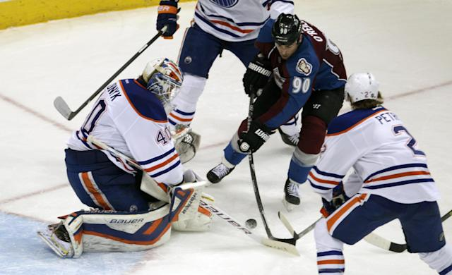 Edmonton Oilers goalie Devan Dubnyk (40) challenges Colorado Avalanche center Ryan O'Reilly (90) as Oilers defenseman Jeff Petry (2) defends during the third period of an NHL hockey game in Denver on Thursday, Dec. 19, 2013. Colorado won 4-2. (AP Photo/Joe Mahoney)