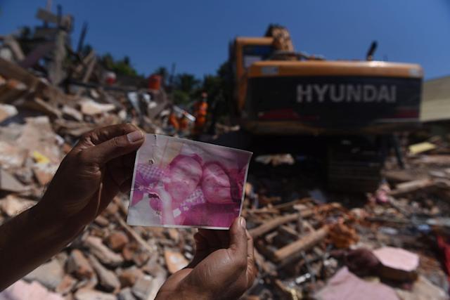 <p>A resident shows a photo of missing victims believed to be trapped inside a collapsed building, as rescue workers continue searching after Sunday's earthquake in Pemenang, North Lombok, Indonesia, Aug. 8, 2018. (Photo: Antara Foto/Zabur Karuru via Reuters) </p>