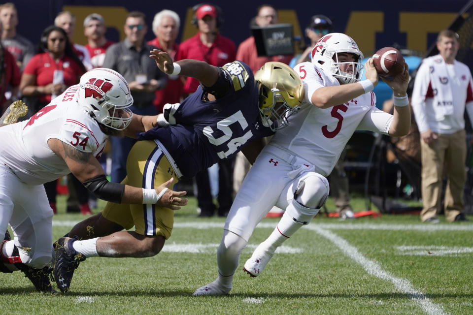 Wisconsin quarterback Graham Mertz (5) makes a two-handed pass to avoid the pressure from Notre Dame defensive lineman Jacob Lacey after Lacey got past lineman Kayden Lyles during the first half of an NCAA college football game Saturday, Sept. 25, 2021, in Chicago. (AP Photo/Charles Rex Arbogast)