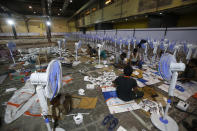 Laborers working to set up at COVID-19 field hospital in Mumbai, India, Thursday, April 22, 2021. New infections are rising faster in India than any other place in the world, stunning authorities and capsizing its fragile health system. (AP Photo/Rafiq Maqbool)