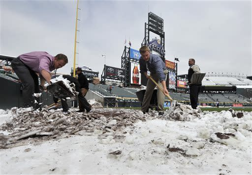 Coors Field grounds crew and stadium employees shovel snow before the start of a baseball doubleheader between the New York Mets and Colorado Rockies on Tuesday, April 16, 2013, in Denver. (AP Photo/Jack Dempsey)