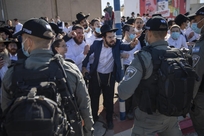 File - In this Sunday, Jan. 24, 2021 file photo, Ultra-Orthodox Jews argue with Israeli border police officers during a protest over the coronavirus lockdown restrictions, in Ashdod, Israel. (AP Photo/Oded Balilty, File)