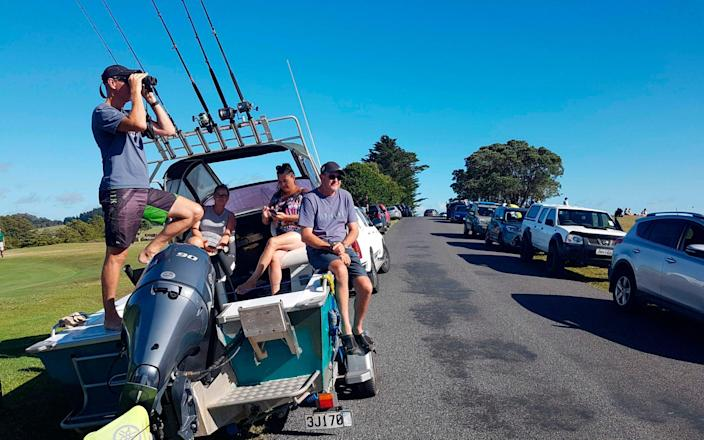 John Fitzgerald, left, on holidays with his wife Rita and friends, scans the horizon from high ground for any sign of a tsunami near Waitangi, New Zealand - AP