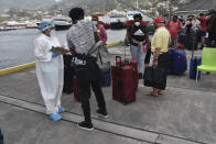 British, Canadian and U.S. nationals wait to board the Royal Caribbean cruise ship Reflection to be evacuated free of charge, in Kingstown on the eastern Caribbean island of St. Vincent, Friday, April 16, 2021. La Soufriere volcano has shot out another explosive burst of gas and ash Friday morning as the cruise ship arrived to evacuate some of the foreigners who had been stuck on a St. Vincent island by a week of violent eruptions. (AP Photo/Orvil Samuel)