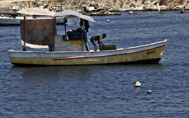 In this photo taken on Wednesday, July 31, 2013, a Palestinian fisherman works on his boat at the fishermen sea port in Gaza City. Regime change in Egypt has cost the Hamas rulers of Gaza their most important foreign ally, and ordinary Palestinians are being caught up in the animosity. Many Gazans were laid off after Egypt closed the territory's border, and Palestinians living in Egypt are keeping a low profile for fear of being targeted in the backlash against Hamas. (AP Photo/Adel Hana)