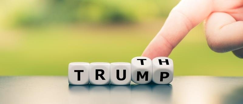 """Hand turns dice and changes the name """"Trump"""" to """"Truth""""."""