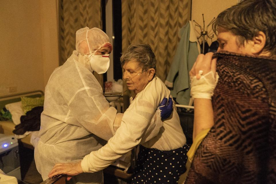 A medical worker helps a patient with COVID-19 to get up in a hospital in Rudky, Western Ukraine, on Tuesday, Jan. 5, 2021. Ukraine imposed a broad lockdown Friday, but many medical workers in the country fear that it came too late and the long holidays, during which Ukrainians frequented entertainment venues, attended festive parties and crowded church services, will trigger a surge in new coronavirus infections. (AP Photo/Evgeniy Maloletka)