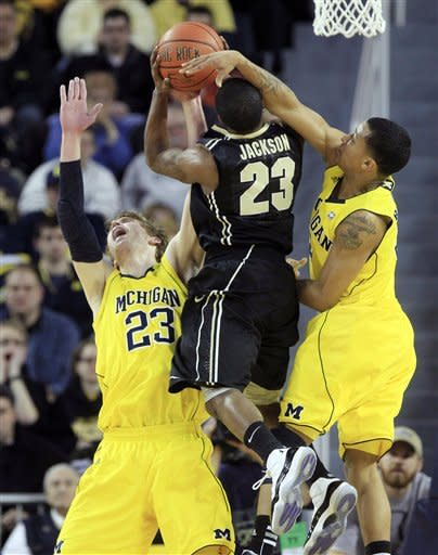 Purdue guard Lewis Jackson (23) shoots over the defense of Michigan forward Evan Smotrycz (23) and guard Trey Burke during the first half of an NCAA college basketball game at Crisler Center in Ann Arbor, Mich., Saturday, Feb. 25, 2012. (AP Photo/Carlos Osorio)