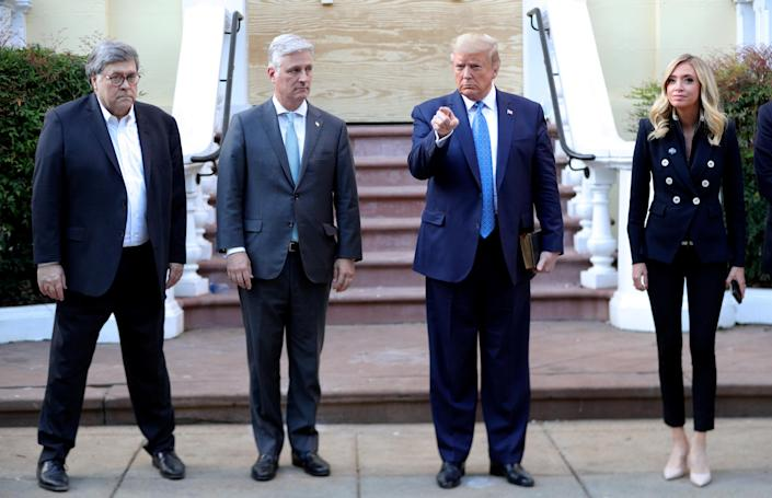 Standing in front of St. John's Church on June 1, from left: Attorney General William Barr, national security adviser Robert O'Brien, President Trump and White House press secretary Kayleigh McEnany. (Tom Brenner/Reuters)