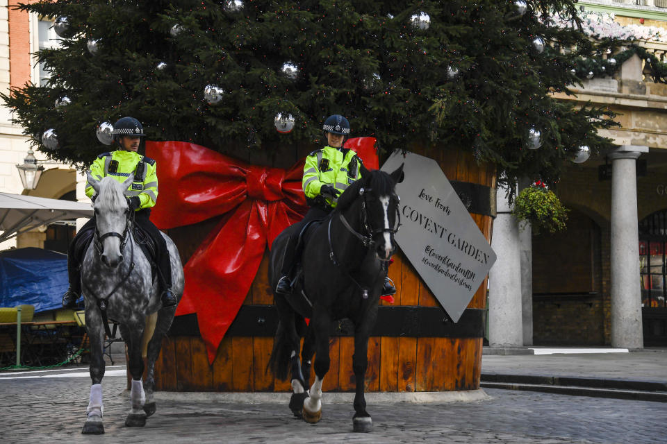 Two police officers ride their horses backdropped by a Christmas tree in Covent Garden, in London, Tuesday, Nov. 24, 2020. Haircuts, shopping trips and visits to the pub will be back on the agenda for millions of people when a four-week lockdown in England comes to an end next week, British Prime Minister Boris Johnson said Monday. (AP Photo/Alberto Pezzali)