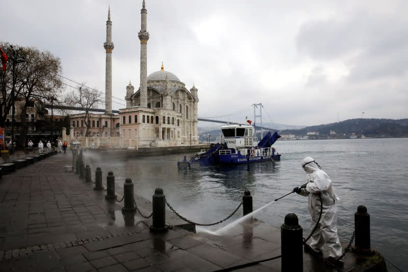 FILE PHOTO: A worker sprays disinfectant outside Ortakoy Mosque, to prevent the spread of coronavirus disease (COVID-19), in Istanbul