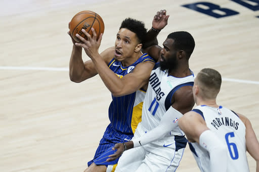 Indiana Pacers' Malcolm Brogdon (7) goes to the basket against Dallas Mavericks' Tim Hardaway Jr. (11) during the first half of an NBA basketball game, Wednesday, Jan. 20, 2021, in Indianapolis. (AP Photo/Darron Cummings)