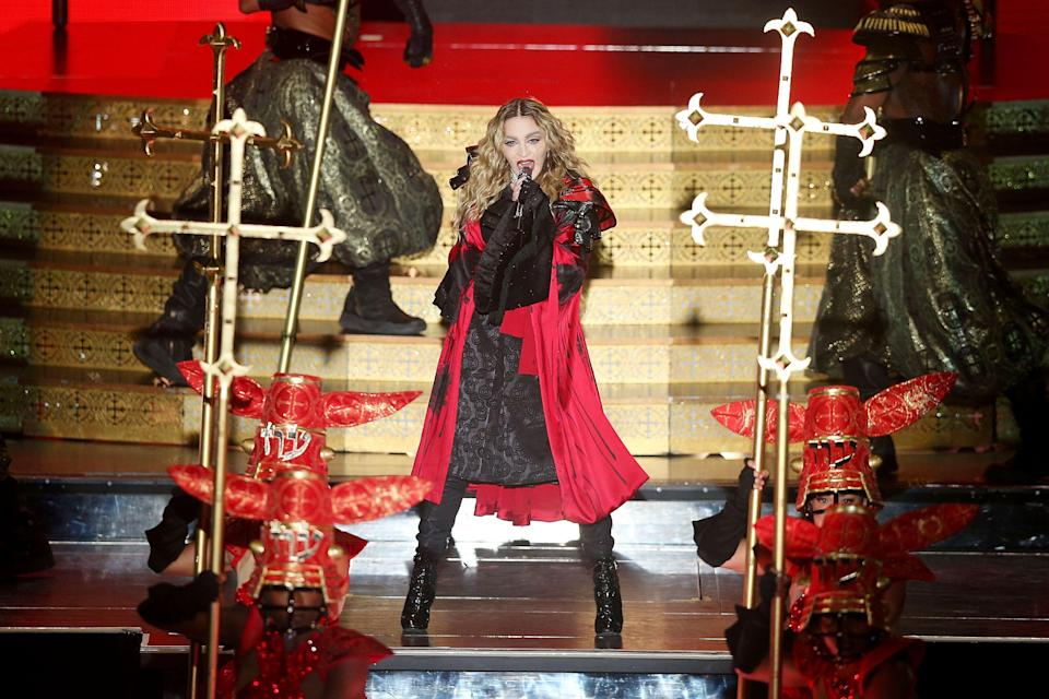 """<p>Her 2015-2016 Rebel Heart Tour featured this red kimono designed by <a href=""""https://www.refinery29.com/2012/12/41146/madonna-style"""" rel=""""nofollow noopener"""" target=""""_blank"""" data-ylk=""""slk:Arianne Phillips"""" class=""""link rapid-noclick-resp"""">Arianne Phillips</a> for the downright medieval opening portion of the show, where Madge and dancers brandished (surprise!) enormous crucifixes like weapons. """"I like crosses,"""" <a href=""""https://www.rollingstone.com/music/features/madonna-on-making-rebel-heart-the-age-of-distraction-and-joan-of-arc-20150305"""" rel=""""nofollow noopener"""" target=""""_blank"""" data-ylk=""""slk:she told Rolling Stone in 2015"""" class=""""link rapid-noclick-resp"""">she told <em>Rolling Stone</em> in 2015</a>. """"I'm sentimental about Jesus on the cross. Jesus was a Jew, and also I believe he was a catalyst, and I think he offended people because his message was to love your neighbor as yourself; in other words, no one is better than somebody else. He embraced all people, whether it was a beggar on the street or a prostitute, and he admonished a group of Jews who were not observing the prophets of the Torah. So he rattled a lot of people's cages.""""</p><span class=""""copyright"""">Photo: Graham Denholm/Getty Images.</span>"""