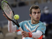 France's Hugo Gaston plays a shot against Austria's Dominic Thiem in the fourth round match of the French Open tennis tournament at the Roland Garros stadium in Paris, France, Sunday, Oct. 4, 2020. (AP Photo/Alessandra Tarantino)