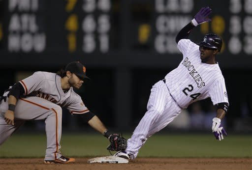 Colorado Rockies baserunner Dexter Fowler (24) slides safely into second base on an extra base single while San Francisco Giants shortstop Brandon Crawford applies the tag in the fourth inning of their baseball game in Denver, Wednesday, April 11, 2012. (AP Photo/Joe Mahoney)