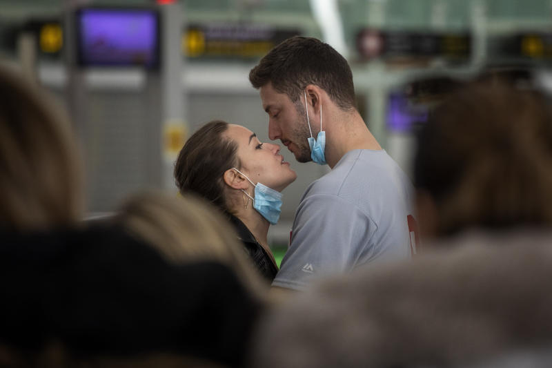 A couple kiss, at the Barcelona Airport, Spain, Thursday, March 12, 2020. Airlines and travelers are still sorting out the new travel ban that President Donald Trump announced late Wednesday, barring most foreign visitors from continental Europe for 30 days. (AP Photo/Emilio Morenatti)
