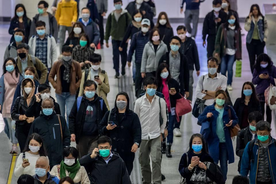Commuters wearing protective masks walk through a station in Hong Kong. Source: Getty