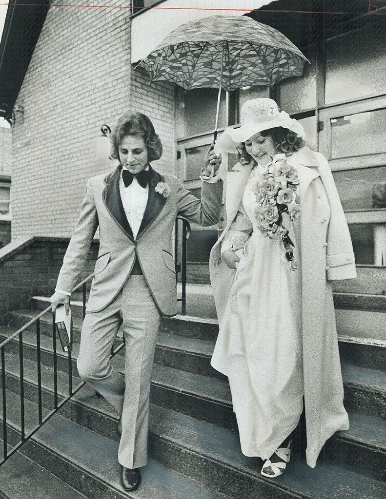 """<p>The weather doesn't cramp this couple's style as they leave the church. The bride also has another layer of protection for her 'do in the form of a lace hat. </p><p><a href=""""http://www.goodhousekeeping.com/beauty/nails/g3720/wedding-nail-designs/"""" rel=""""nofollow noopener"""" target=""""_blank"""" data-ylk=""""slk:17 creative nail ideas for weddings »"""" class=""""link rapid-noclick-resp""""><em>17 creative nail ideas for weddings »</em></a></p>"""