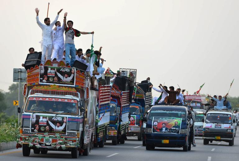 Supporters of Pakistani cricketer-turned-politician Imran Khan travel in Swabi on August 14, 2014, as they head towards Islamabad in a bid to unseat the government