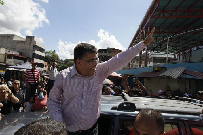 Elias Jaua, top, Venezuela's former Vice President and candidate for governor of Miranda state, waves to supporters after casting his ballot at a polling station in Caracas, Venezuela, Sunday, Dec. 16, 2012. Venezuelans are choosing governors and state lawmakers in elections that have become a key test of whether President Hugo Chavez's movement can endure if the leader leaves the political stage. (AP Photo/Ariana Cubillos)