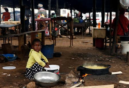 A child sits amongst vendors stalls in Mbare township, Harare, Zimbabwe, January 23, 2019. REUTERS/Philimon Bulawayo