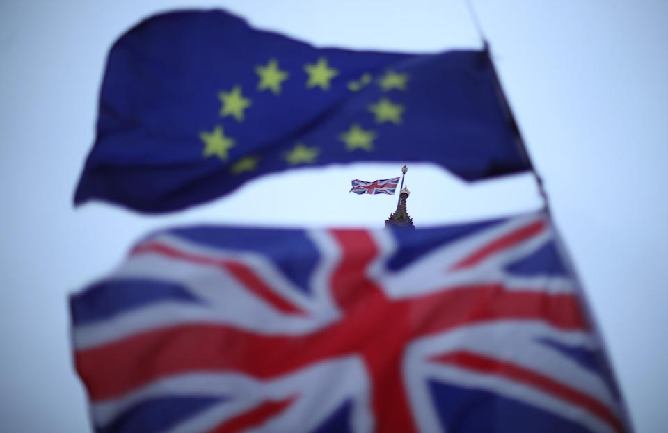 The EU and Union flags flying outside Parliament in Westminster, London. Theresa May will intensify efforts to win over her Brexit critics and seek fresh guarantees from Brussels ahead of next week's crunch vote on her deal.