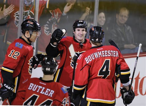 Calgary Flames' Curtis Glencross, centre, celebrates his goal against the Minnesota Wild with Jay Bouwmeester, right, and Jarome Iginla during first period NHL action in Calgary, Alberta, Tuesday Dec. 20, 2011. (AP Photo/The Canadian Press, Larry MacDougal)