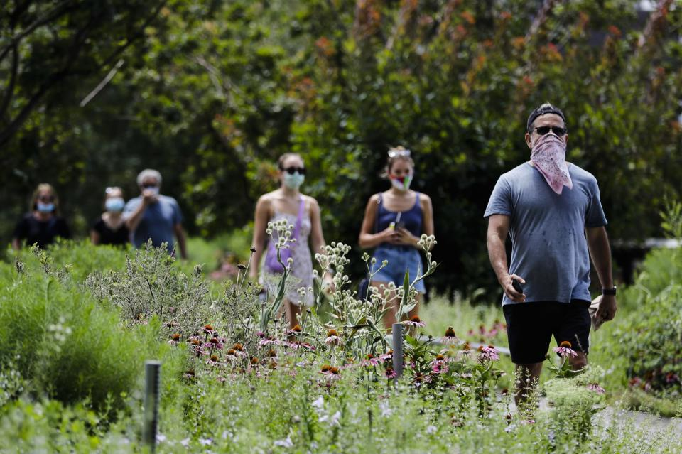 People walk along the High Line Park, Thursday, July 16, 2020, in New York. The Highline opened today after having been closed the last few months during the pandemic. (AP Photo/Frank Franklin II)