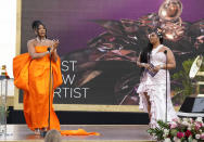 Megan Thee Stallion accepts the award for best new artist as presenter Lizzo, right, looks on at the 63rd annual Grammy Awards at the Los Angeles Convention Center on Sunday, March 14, 2021. (AP Photo/Chris Pizzello)
