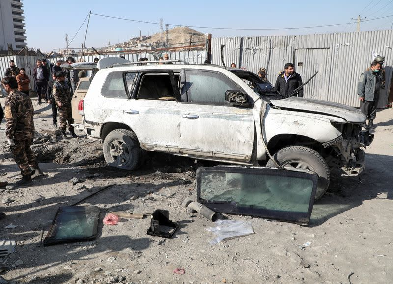 Afghan security officials inspect the site of a bomb blast in Kabul, Afghanistan